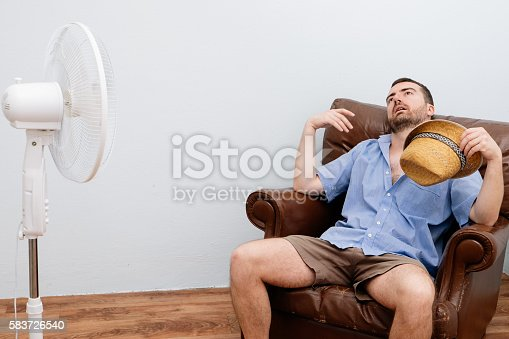 istock Flushed man feeling hot in front of a fan 583726540