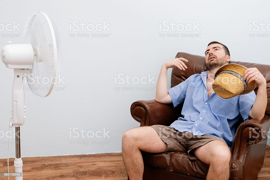 Flushed man feeling hot in front of a fan - foto de stock