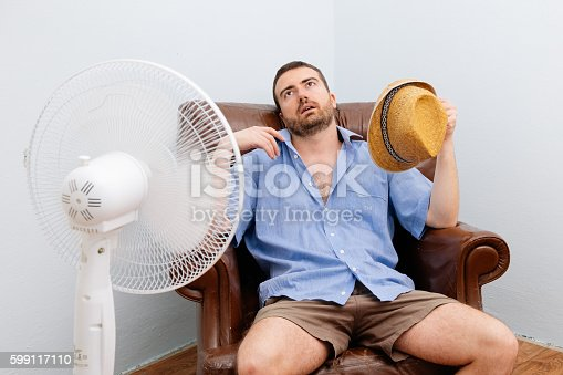 istock Flushed man feeling hot in front of a fan 599117110