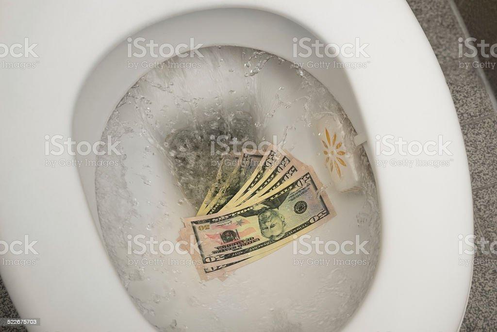 Flushing money down the toilet stock photo
