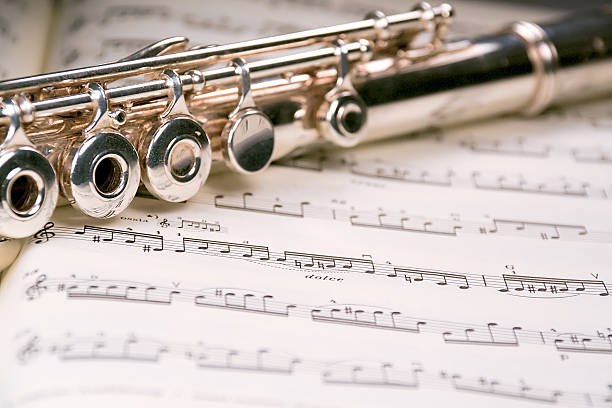 flute across a musical score - musical instrument stock photos and pictures