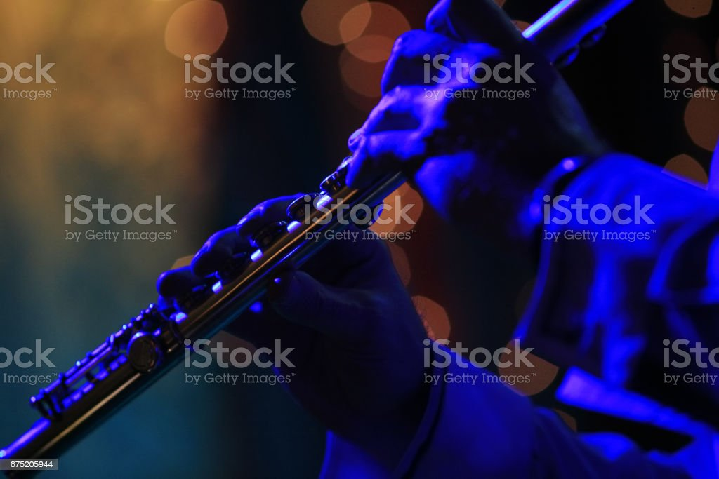 Flute in hands of the musician with scenic light stock photo