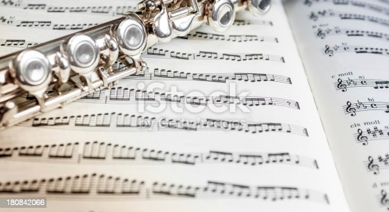 Close up of a silver flute on a sheet of music notes. Light colour cast and vignette effect.Photos from the same series: