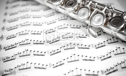 Close up of a silver flute on a sheet of music notes. Black and white strong contrast and vignette effect.
