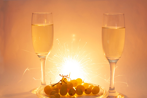 Fluted glasses with Champagne next to grapes for White Christmas celebrations and Happy New Years holidays