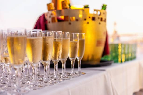 Flutes of champagne at luxury event Glasses full of champagne arranged on table in a row at luxury event. epernay stock pictures, royalty-free photos & images