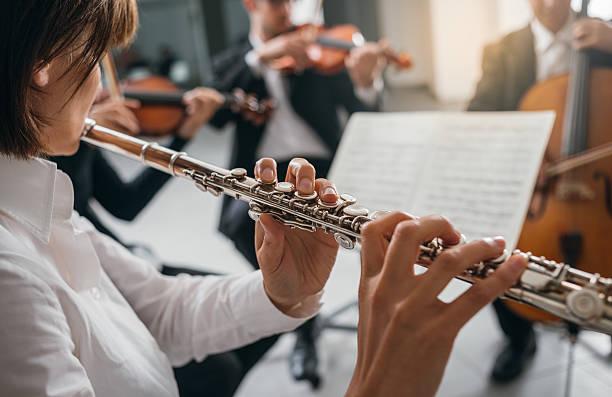 ihr flutist instrument spielen auf der bühne - philharmonie stock-fotos und bilder