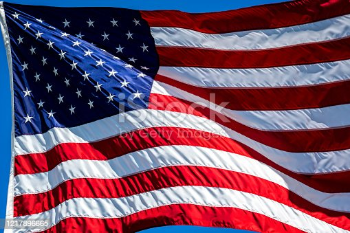 840615050 istock photo Fluttering silk flag of United States of America 1217896665