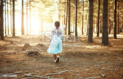 Rear view shot of a little girl walking in the woods while dressed up as a fairy