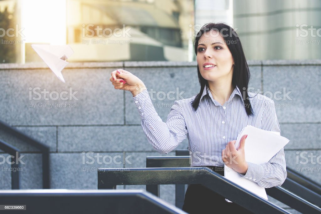 Fly away. Portrait of attractive and cheerful business woman in smart casual wear launching paper plane while standing against office building. royalty free stockfoto