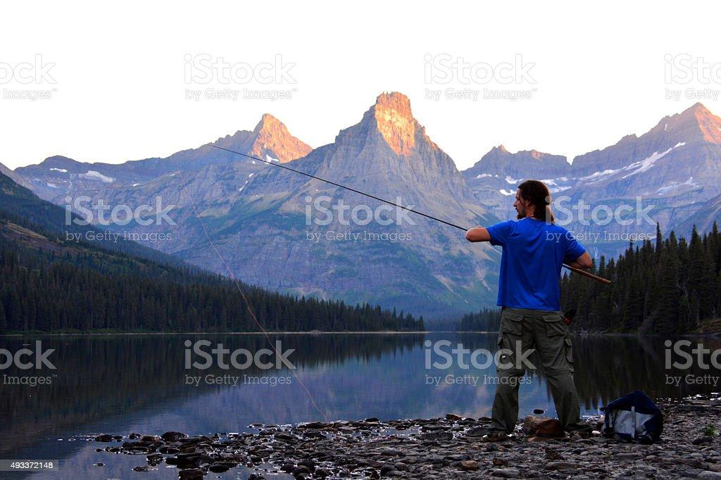 Fly Fisherman Adjusts Rod stock photo
