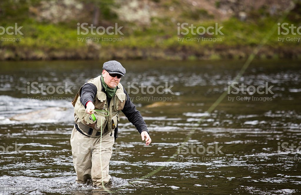 Fly fisherman grey cap sunglasses vest stock photo
