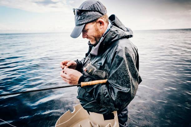 fischer, binden einer fliege auf seine linie zu fliegen. - angeln dänemark stock-fotos und bilder