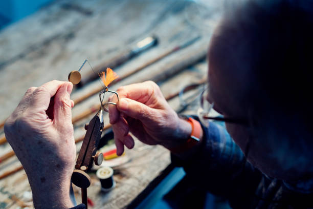 Fly Fisherman Tying Flies For Ready For Fishing - foto stock