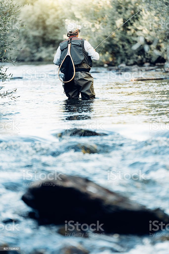 Fly fisherman using flyfishing rod. – Foto