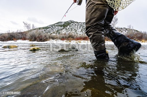 Fly Fisherman Wading in River - Winter fly fishing recreation.