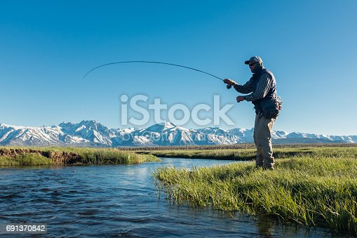 Fly Fishermen Along The Spring Mountain Stream fighting a trout.