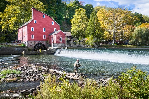 Clinton, New Jersey, USA - October 17, 2015: A mature fisherman fly fishes on the Raritan River just below the falls by the  200 year old Red Mill in Clinton, New Jersey.