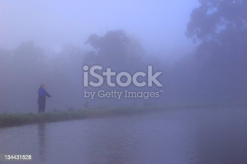 Lady fly fishing along the bank of a lake in the mist.