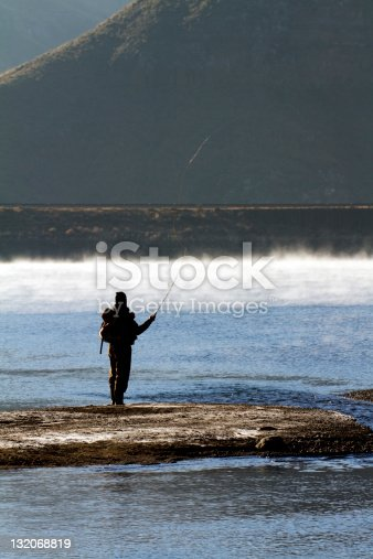 Silhouette of a man fly fishing in misty early morning water. This was shot at the Katse dam in Lesotho.