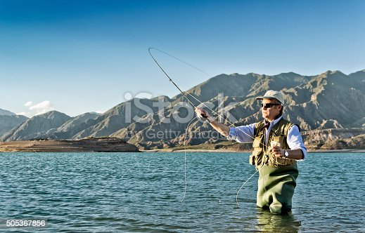 Fly fishing on lake for catching trout. Mendoza, Argentina.