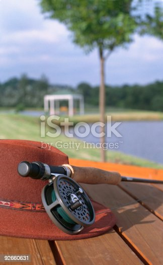 Fly fishing reel and hat. Still life next to Trout Dam