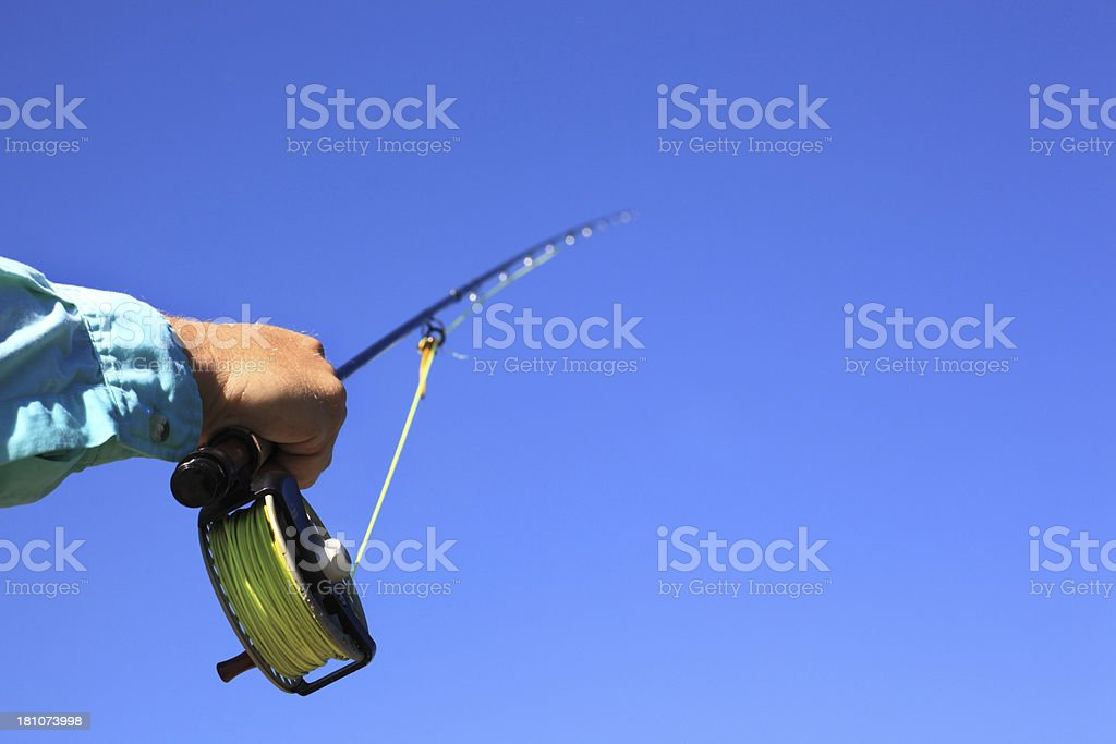 fly fishing rod and reel against blue sky royalty-free stock photo