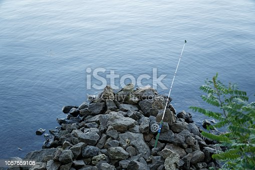 1094918172 istock photo Fly fishing rod and reel on stone river bank. Fishing scene on the banks 1057559108