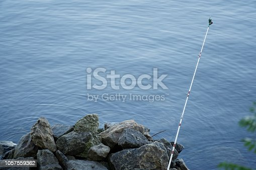 1094918172 istock photo Fly fishing rod and reel on stone river bank. Fishing scene on the banks 1057559362