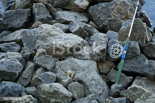 1094918172 istock photo Fly fishing rod and reel on stone river bank. Fishing scene on the banks 1057562676