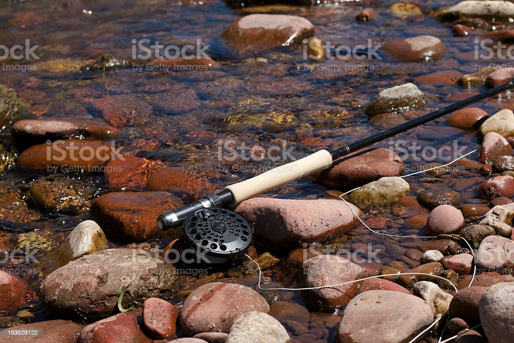Fly Fishing Rod on rocks stock photo