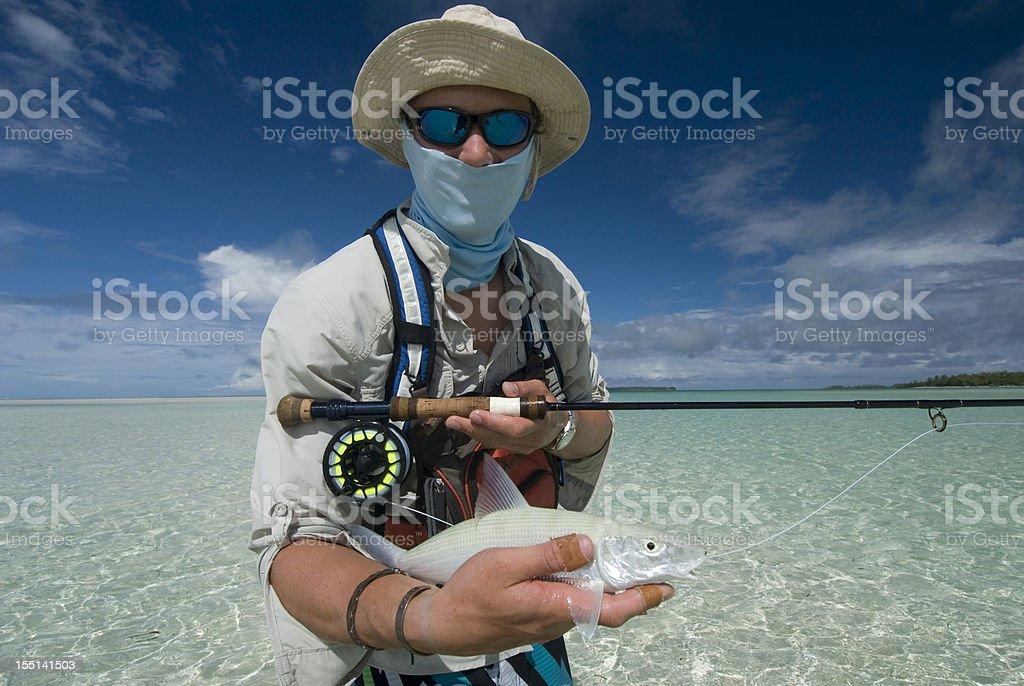 fly fishrman with his catch stock photo