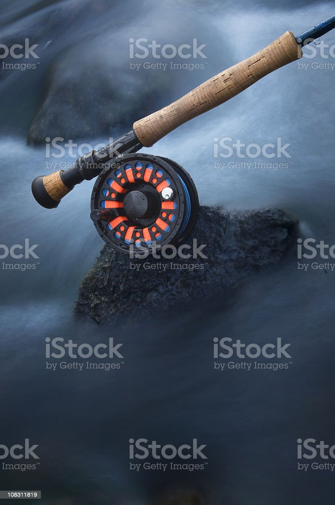 Fly rod and reel in icy cold creek stock photo