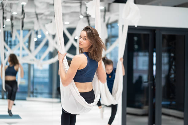 Fly yoga. Young woman practices aerial anti-gravity yoga stock photo
