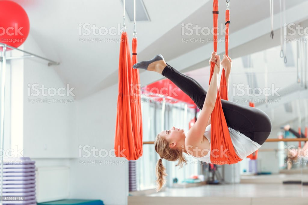 Fly yoga. Young woman practices aerial anti-gravity yoga with a hammock . stock photo