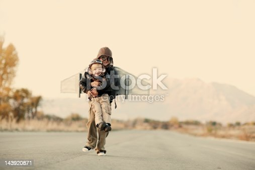 A young boy takes his little brother to the sky with his rocket pack. Plenty of great copy space for your concept.