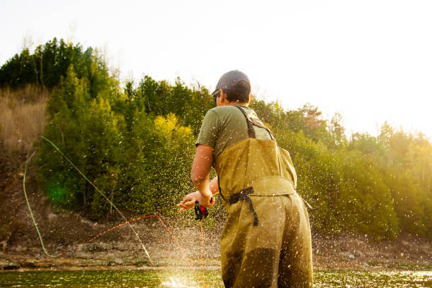 A fly-fisherman casting double handed Spey rod in warm afternoon light. stock photo