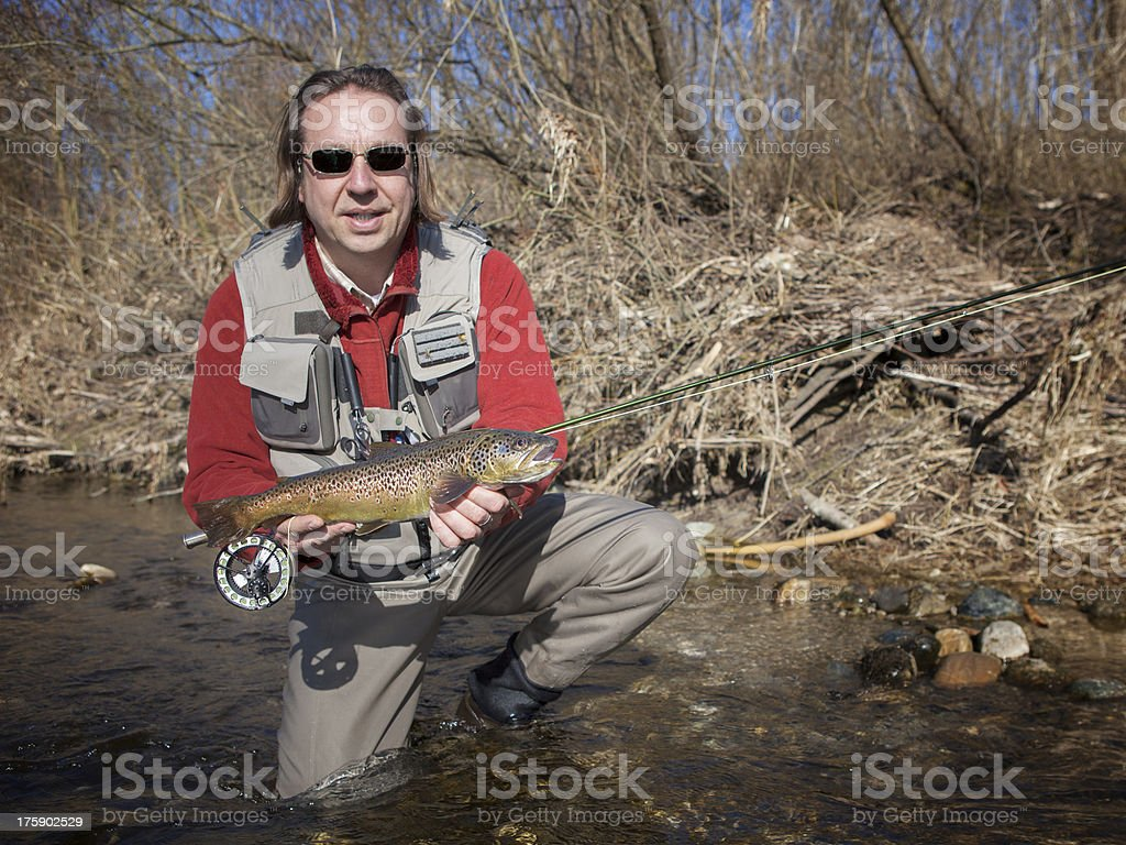 Flyfisherman holding a brown trout royalty-free stock photo