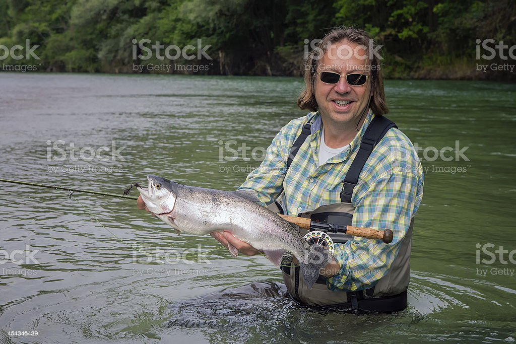 Flyfisherman holding a rainbow trout royalty-free stock photo