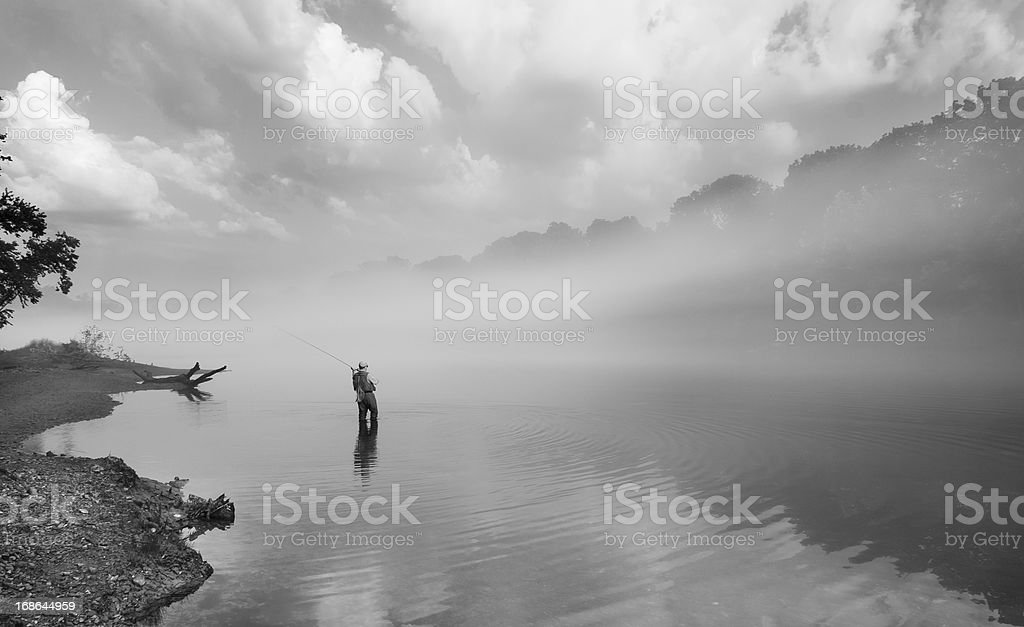 Flyfisherman in the early morning fog royalty-free stock photo