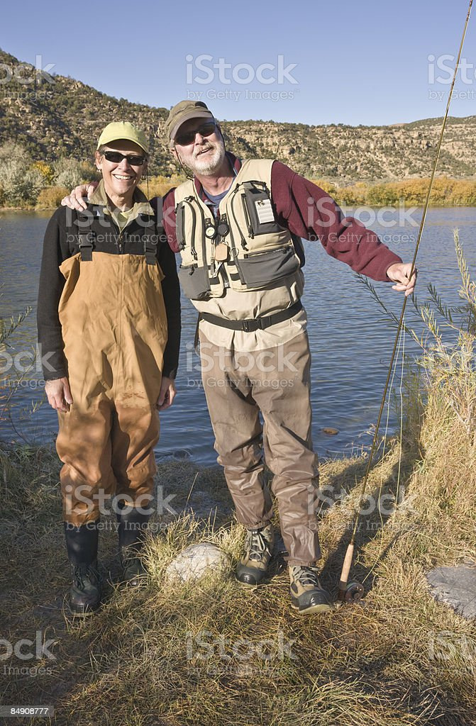 Fly-fishing couple wearing waders. royalty-free stock photo