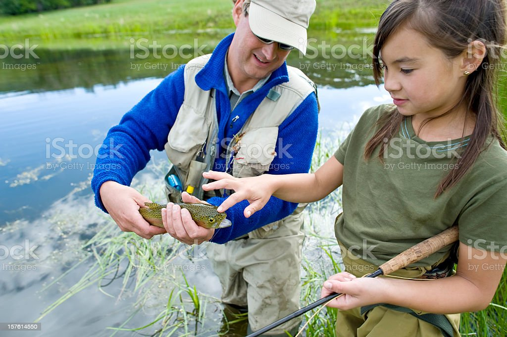 Flyfishing father and daughter look at their catch stock photo