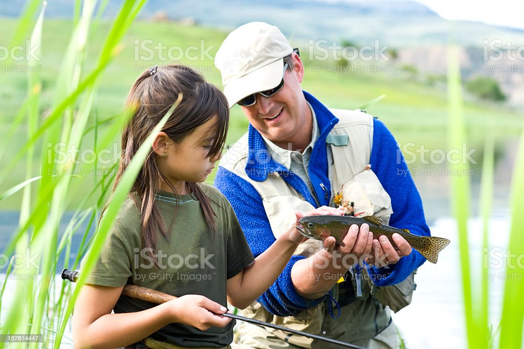 Flyfishing father teaching daughter how to fish stock photo
