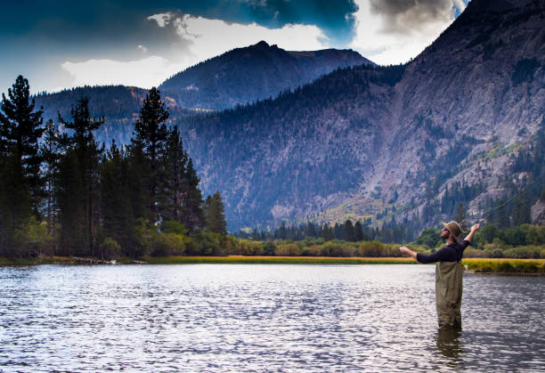 Fly-Fishing in Paradise A single man in waiters stands in the water and fly-fishes in front of a breathtaking mountain backdrop. casting stock pictures, royalty-free photos & images