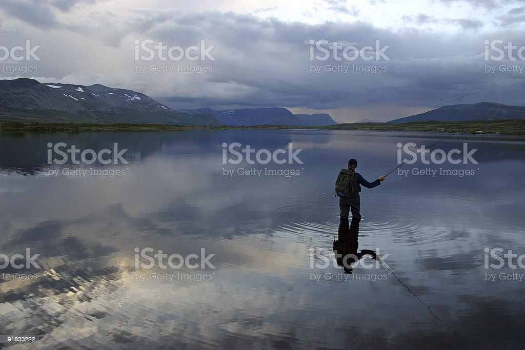 Flyfishing in water surrounded by mountains stock photo