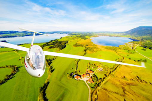 young woman flying a glider plane over a beautiful landscape.