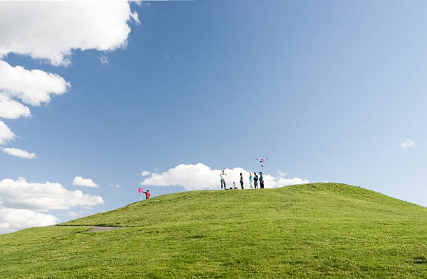 Flying a kite on hill with blue sky and clouds stock photo