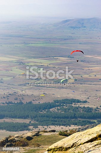 istock Flying a paraglider in the sky over the mountains, aerial pilot pov, vertical 946568434