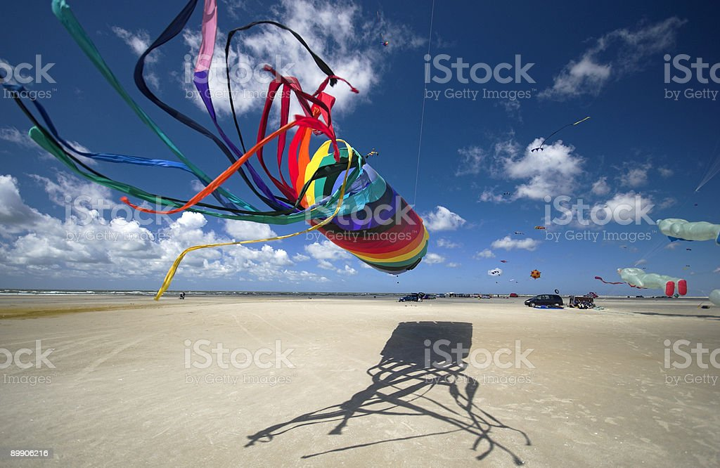 Flying a rainbow colored kite over a beach royalty-free stock photo
