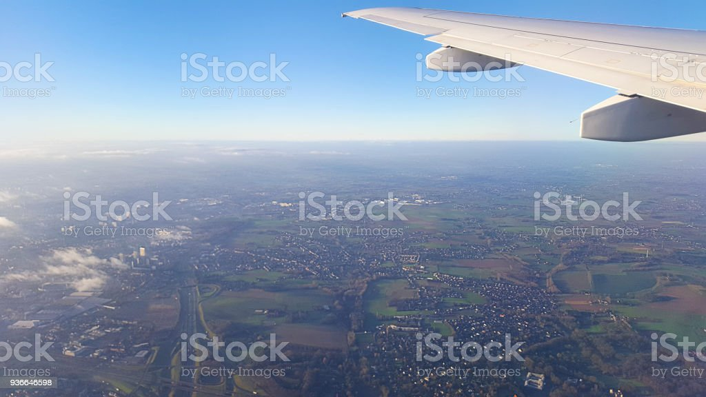 Flying above Belgium at sunrise with hazy sun coming up behind the...